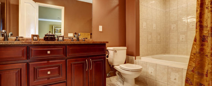 32040156 - bathroom in brown color with beige tile trim. modern wooden cabinet with granite top and mirror