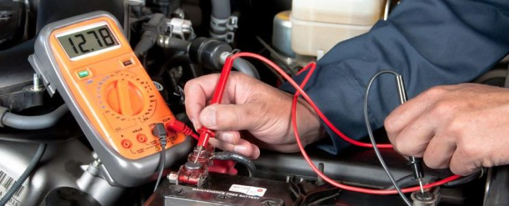 7909467 - an auto mechanic uses a multimeter voltmeter to check the voltage level in a car battery.