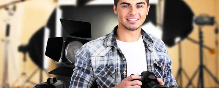 36370674 - young photographer with camera on photo studio background