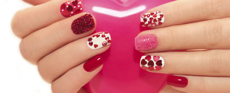 35512428 - manicure with rhinestones in the shape of hearts and pink balls on white and red nail polish on a white background.