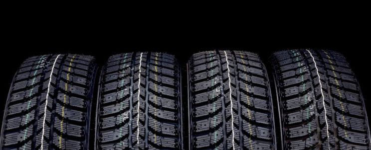 35121984 - winter car tires isolated on black background