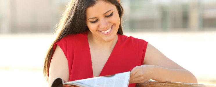 44711563 - happy fashion woman reading a magazine in an urban park wearing a red blouse