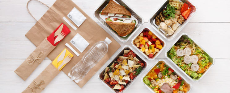59486675 - healthy food delivery. take away for diet. fitness nutrition, vegetables, meat and fruits in foil boxes, cutlery, water and brown paper package. top view, flat lay at white wood with copy space