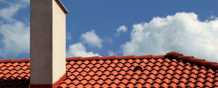 15365932 - red tiles roof and chimney with blue sky