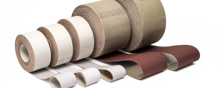 61494151 - sandpaper in rolls for industrial use in different sizes and thickness on white background