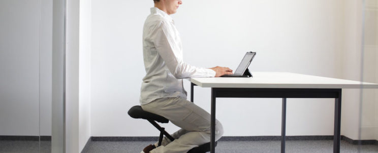22284943 - correct sitting position at desk with tablet  man on kneeling chair