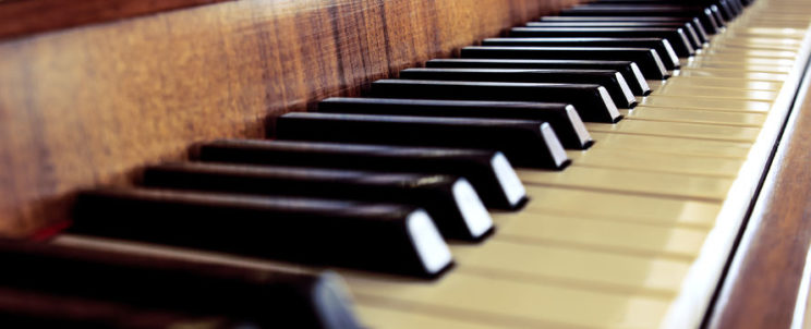 50568534 - black and white piano keyboard brown wooden close-up, background