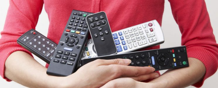 Woman Holding Armful Of TV And Audio Remote Controls